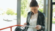 Young woman using digital tablet on tram/train. video