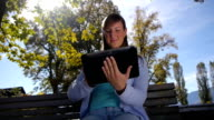 DOLLY: Young woman using digital tablet video