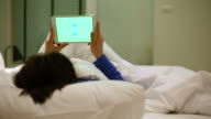 Young woman using Digital tablet with Green screen on bed, 4K(UHD) video