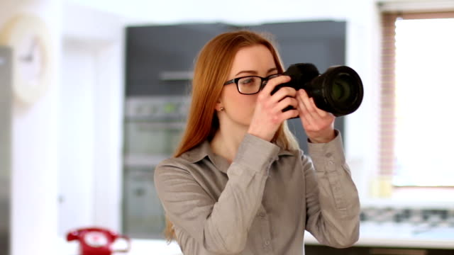 Young woman using DSLR, home interior. video
