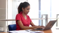 Young woman using laptop in modern office, typing on keyboard video