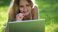 Young woman using laptop in park video
