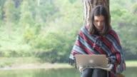 Young woman using laptop near a green lake video