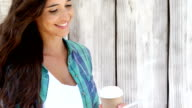 Young woman using mobile phone and having coffee from disposable cup video