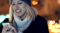 Young woman using mobile phone in a city at night. video