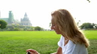 Young woman using mobile phone in a park video