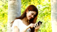 Young woman using mobile phone. video