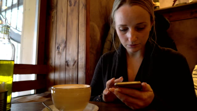 young woman using phone in a cafe video