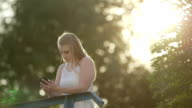Young woman using smart phone on sunny day video