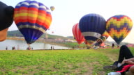 Young woman using smartphone and relex with hot air balloons video