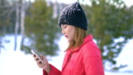 Young Woman using smartphone in winter park video