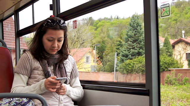 Young woman using smartphone while riding bus video