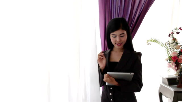 Young woman using tablet and thinking some idea video