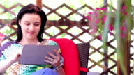 Young woman using tablet computer outside video