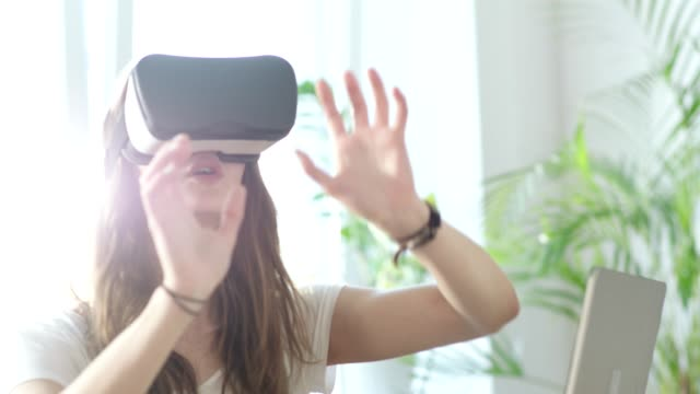 Young woman using virtual reality glasses. Touching big imaginary object video
