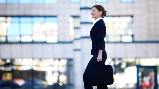 Young  woman walking against the business center. video