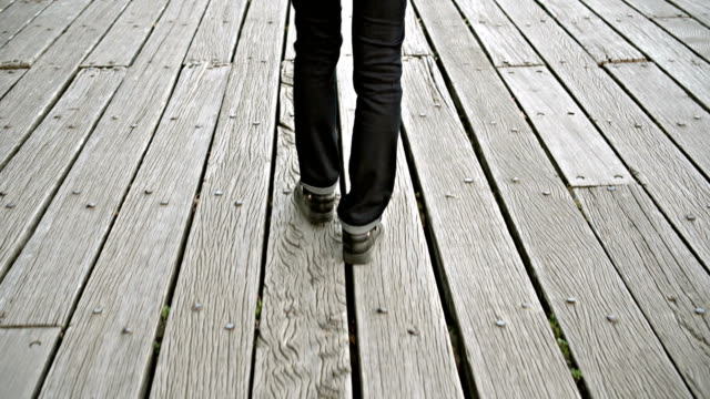 Young woman walking alone on a wooden pier or bridge over river, point of view perspective video