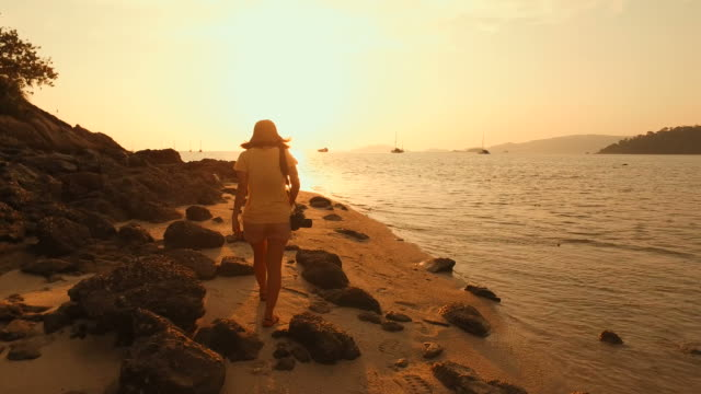 Young Woman Walking Along the Sunset Beach video