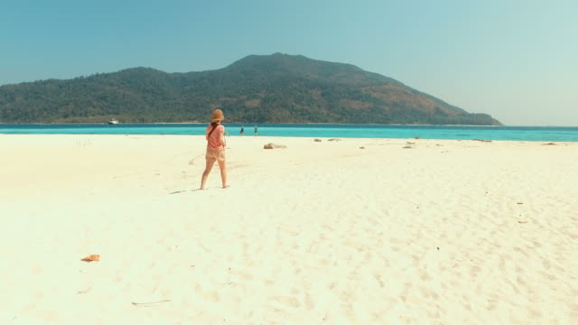 Young Woman Walking Along the White Sand Beach video