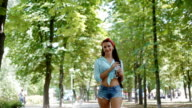 Young woman walking in the park.American style video