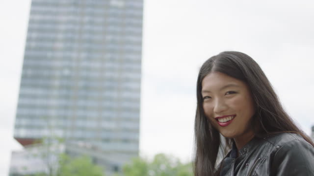 Young woman walking next to skyscraper video