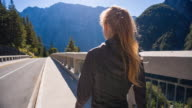 Young woman walking on a concrete bridge in the mountainside video