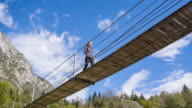Young woman walking on a wooden suspension bridge video