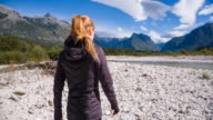 Young woman walking on an empty river bed video