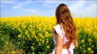 Young Woman Walking through Yellow Field Touching Flowers HD video