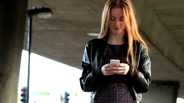 Young woman walking using smartphone. video
