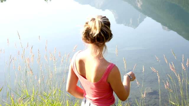 Young woman walks along edge of mountain pond video
