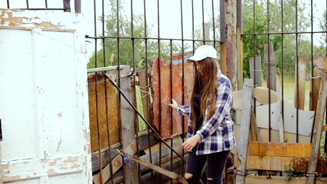 A young woman walks along the iron fence to which the old wooden doors are tied. video