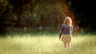 Young Woman Walks Away From Camera Into Open Meadow, She Holds Flower And Day Dreams video