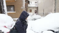 Young woman walks in snowy street. video