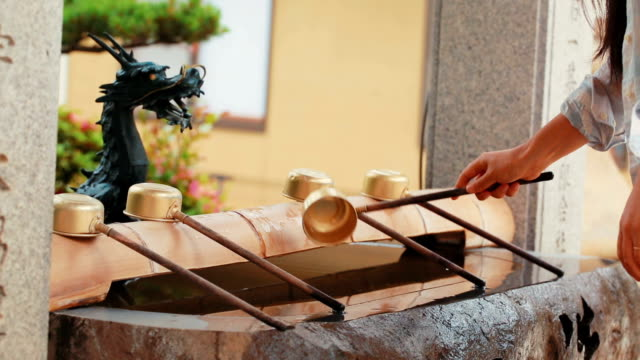 Young Woman washing her hands at a Japanese shrine video
