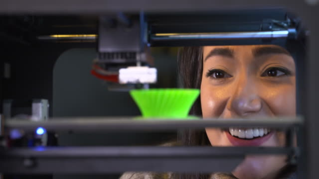 4K: Young woman watching a 3D printer video