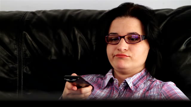 Young woman watching boring movie at TV video