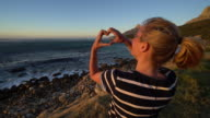 Young woman watching sunset by the coastline, makes heart shape video