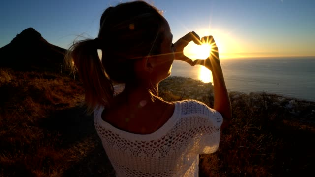 Young woman watching sunset by the sea, makes heart shape video