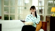 Young woman watching TV and eating popcorn video