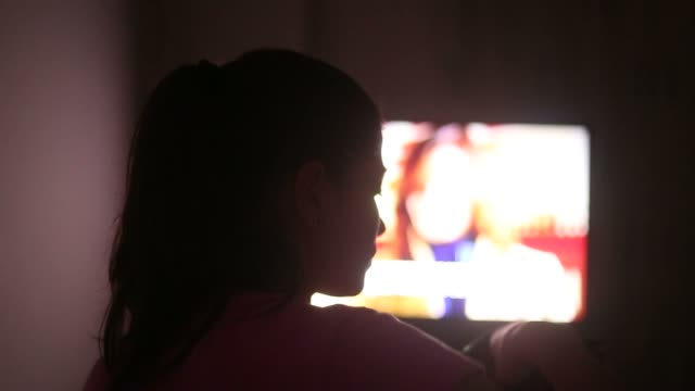 Young woman watching TV late in night. video