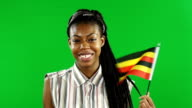 Young woman waving the Uganda flag on Green Screen background video