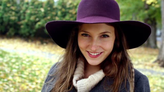 A young woman wearing a hat looks into the camera and smiles video