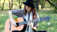Young woman wearing black hat playing guitar in park, summer. video