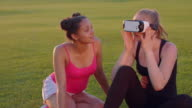 Young woman wearing virtual reality headset. Diverse friends using vr headset video