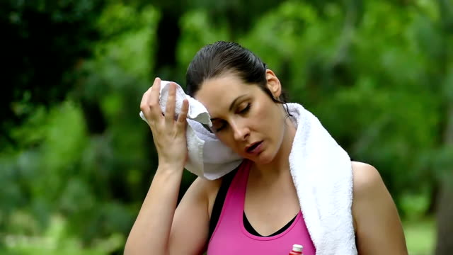 Young woman wipes sweat with a towel during a recreation video