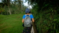 Young woman with a backpack walking along the stone footpath in the green of the jungle. Tourist is actively pursuing their vacation on a tropical island video