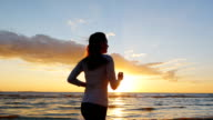Young woman with a beautiful figure running on the beach at sunset. Long hair is beautiful fluttering in the wind. Steadicam slow motion shot video