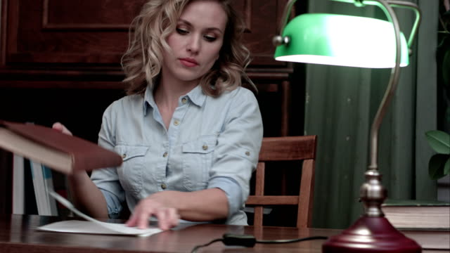 Young woman with a book sits down to the table, turns the green lamp on and starts working video
