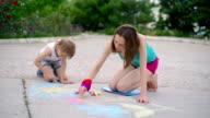 young woman with a child draws a chalk on asphalt, close up video